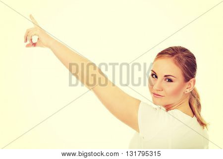 Young woman pointing on copy space or something