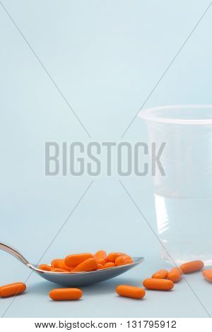 Orange pile of pills in the spoon with glass of water on the gradient blue background
