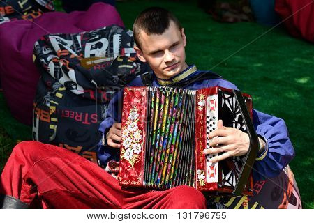 TOMSK RUSSIA - MAY 28 2016: Actor in bright national costume playing the accordion at the Russian Folklore festival