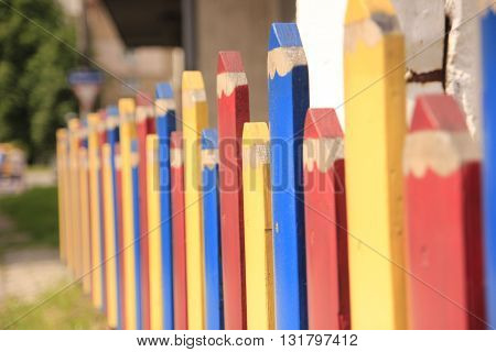 color fence like pencils beyond the house.