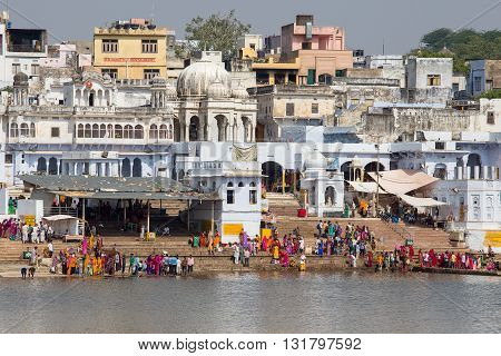 PUSHKAR INDIA - OCTOBER 26 2014: Unidentified people perform puja - ritual ceremony at holy Sarovar lake. Pushkar - famous worship place in India