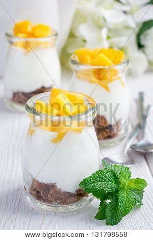 Breakfast dessert with bran flakes plain yogurt and mango on a wooden table