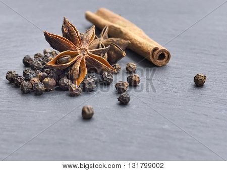 Close-up of christmas spices. Cinnamon, star anise and Pepper on a slate underground.