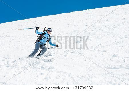 Female skier tackling a steep slope. Ski touring in the mountains.