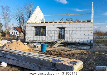 The building is under construction and the materials for construction near the house