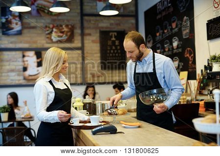 Waiter and waitress working in cafeteria, serving biscuits.