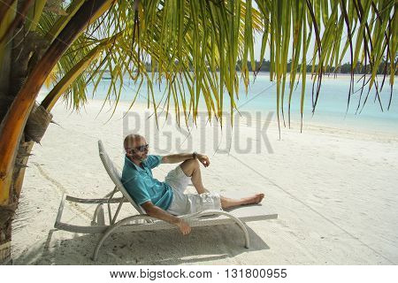 bald man on a sun lounger under a palm tree in the Maldivian beach