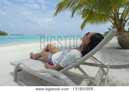 Woman lying on a sun lounger under a palm tree in the Maldivian beach