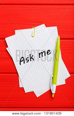 Sheet of paper on red wooden background, ask me