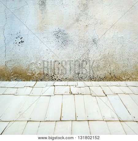 Room interior: grey old cracked painted cement wall texture with wooden floor
