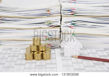 House With Pencil And Stack Of Gold Coins As Tower