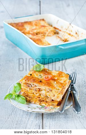 Lasagna slice in the plate on rustic background