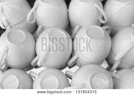 the stack of the white cups of tea in the shelf the white tea cups on the table in black and white tone