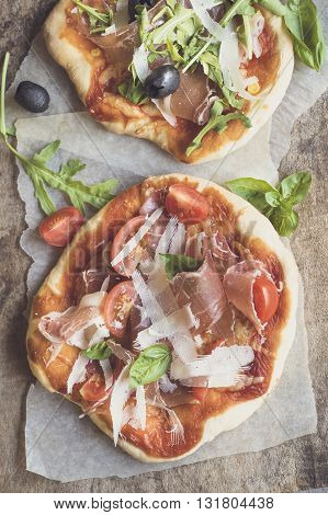 Photos of prosciutto mini pizza on rustic background