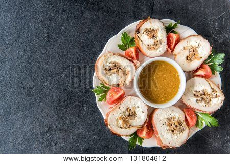 Rolled meat with champignons and sauce on rustic background