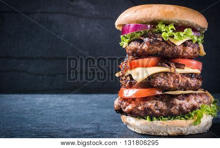 Photos of triple American burger on rustic background