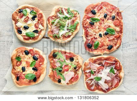 variety of small pizzas on rustic background