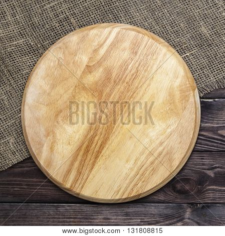 Round cutting board on dark wooden table, top view
