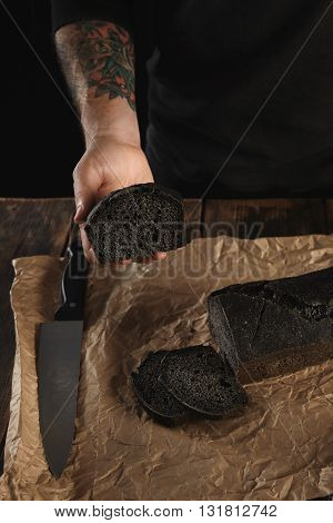 Unrecognizable Baker In Black Sweatshot With Tattooed Hands Shows Piece Of Freshly Baked Homemade Ch