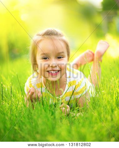 Portrait of a smiling little girl lying on green grass. Cute three years old child enjoying nature outdoors. Healthy carefree kid playing outside in summer park