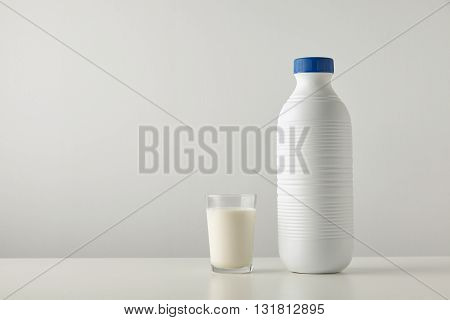 Transparent Glass With Fresh Organic Milk Near Plastic Riffled Blank Bottle With Blue Cap Isolated O