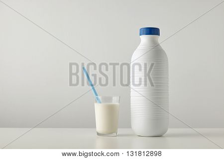 Transparent Glass With Fresh Organic Milk And Blue Drinking Straw Inside Near Plastic Riffled Blank