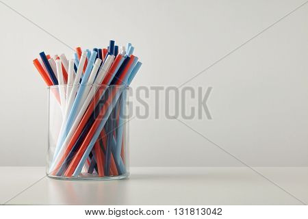 Banch Of Pastel Vivid Colored Thick Drinking Straw In Transparent Glass Pot Isolated On White Table