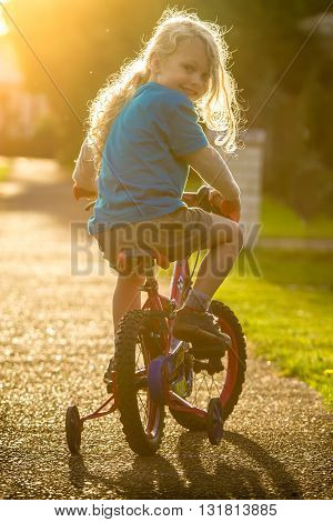smiling young child riding a bike with trainer wheels at sunset