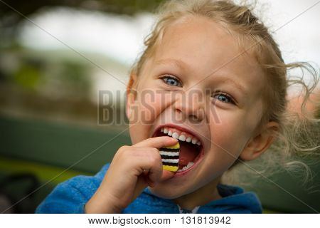 close up of a young blonde haired blue eyed child with mouth wide open about to eat a large sweet.