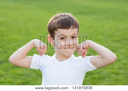 boy in T-shirt standing on a background of green grass and showing muscles