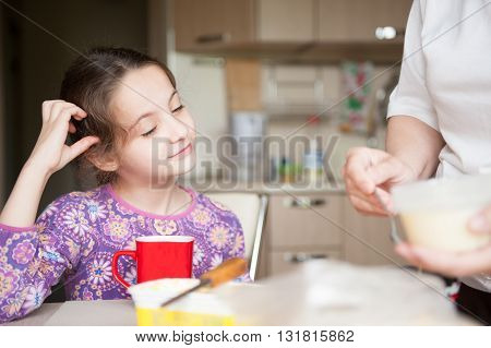 girl sitting in the kitchen waiting to eat
