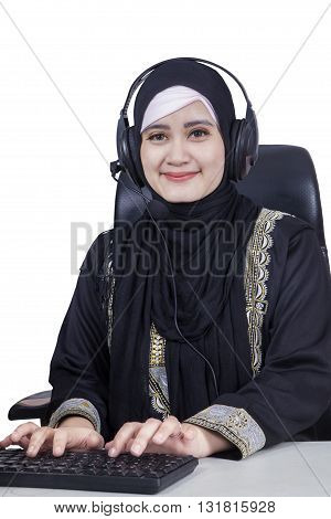 Portrait of middle eastern businesswoman typing on the keyboard while wearing headphones and islamic clothes