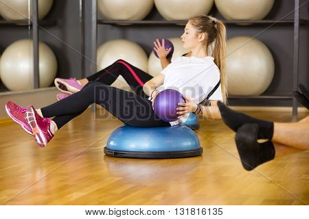 Focused young woman do abdominal workout on half ball and with medicine ball at the fitness class. Core muscle and balance workout. Team and motivation at the gym.