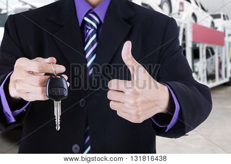 Entrepreneur hands showing thumb up and a car key with trailer truck background carrying new cars