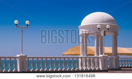 White pavilion at seashore under blue sky