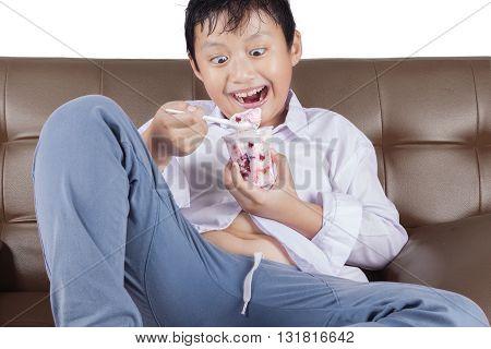 Portrait of a cheerful little boy sitting on the sofa while enjoying ice cream
