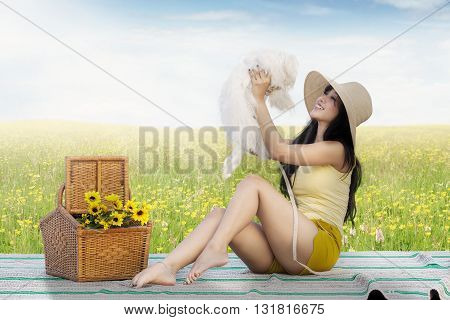 Beautiful young woman sitting on the mat while playing with a maltese dog on the meadow