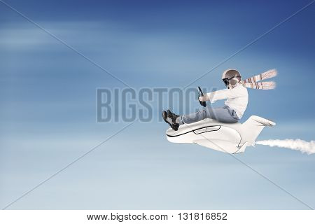 Little boy flying on the sky while driving a small airplane and wearing helmet