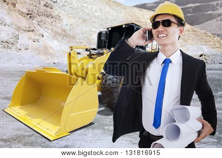Busy contractor talking on the cellphone while carrying blueprints with backhoe on the background shot at mining site