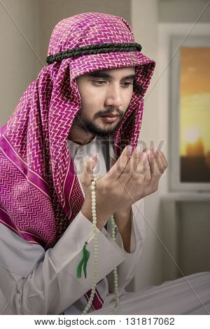 Photo of a devout Arabic person praying at home while wearing headscarf and holding beads