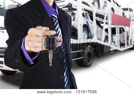 Male driver wearing formal suit and gives a car key with the trailer truck background carrying new cars