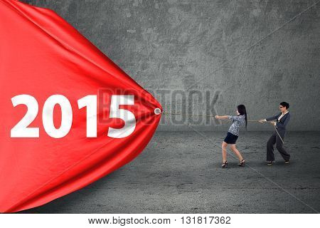 Two female entrepreneur pulling banner with number 2015