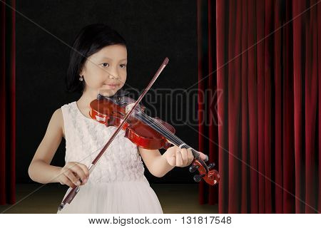 Little Asian girl showing her talent by playing a song with a violin on the stage