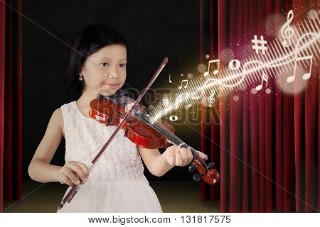 Portrait of attractive little girl playing a song with a violin on the stage