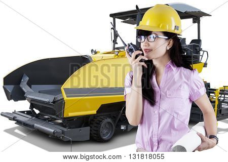 Young forewoman talking on the radio transmitter while holding a blueprint with spreader machine asphalt on the background
