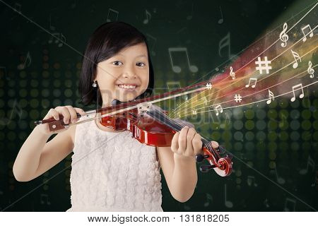 Cute girl smiling at the camera while playing a song with a violin