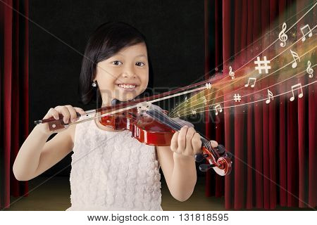 Portrait of happy little girl using a violin while playing a melody on the stage