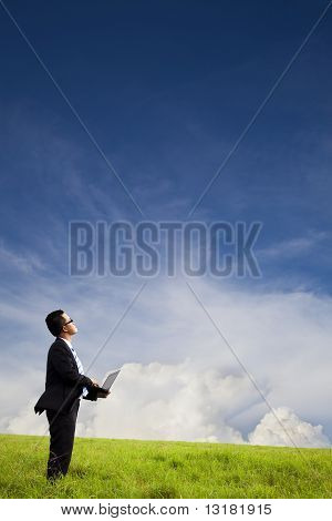 Businessman holding computer and watching the cloud