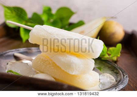 Homemade pear popsicles on metal plate with ice and pears. Summer food concept.