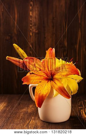 Bunch of orange and yellow lilly flowers on vintage wooden dark table